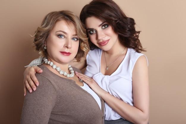 Moeder en volwassen dochter knuffelen, vrouwelijke familieleden. portret van moeder en dochter op een lichte achtergrond in de studio.