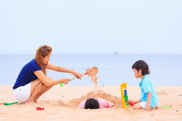 Moeder en zonen spelen op tropisch strand