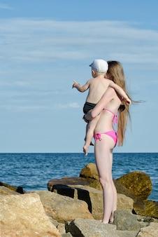Moeder en zoon bevinden zich tussen de stenen aan de kust en kijken in de verte