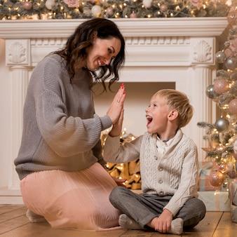 Moeder en zoon die de kerstboom versieren