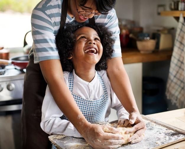 Moeder en zoon die deeg in de keuken kneden
