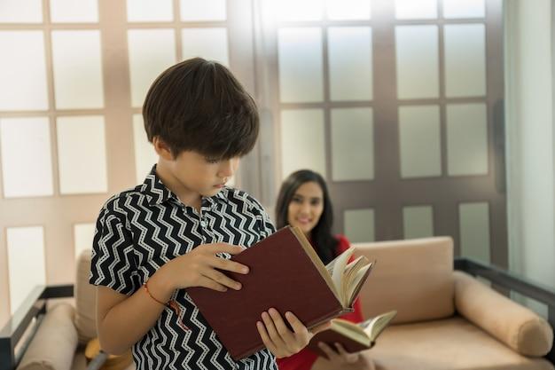 Moeder en zoon die een boek in woonkamer lezen. gelukkig familie concept