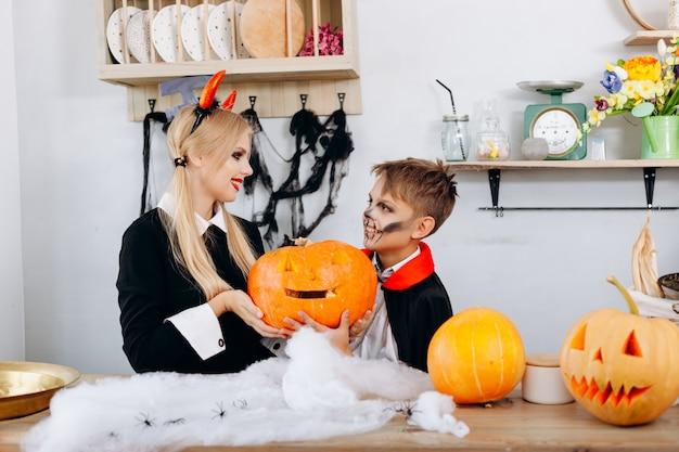 Moeder en zoon die een pompoen houden tijdens voorbereidingen voor halloween.