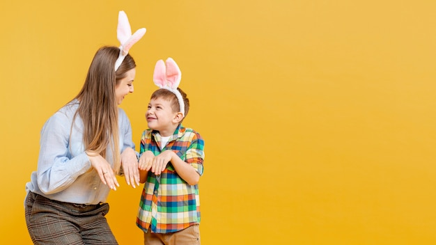 Moeder en zoon die konijn met exemplaar-ruimte imiteren
