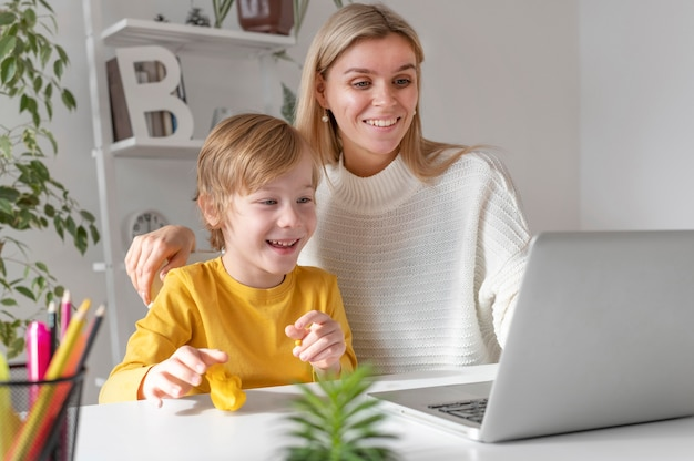 Moeder en zoon die laptop thuis met behulp van
