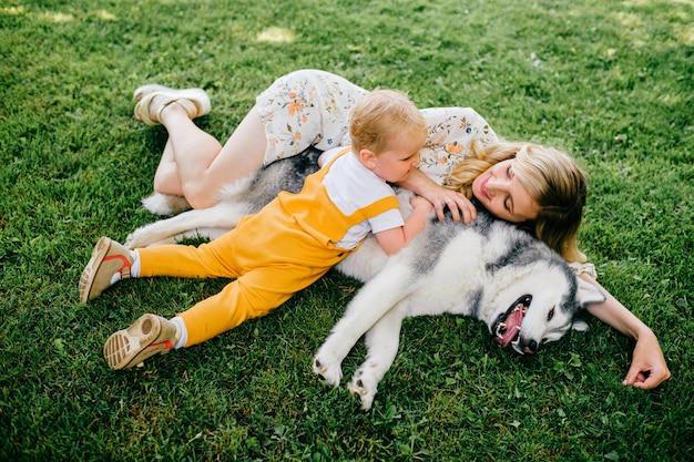 Moeder en zoon die met een hond op het gras liggen