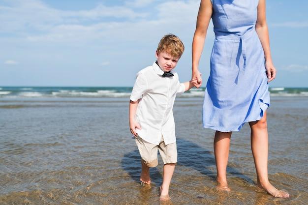 Moeder en zoon die op het strand koelen