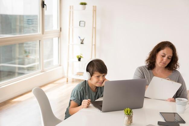Moeder en zoon die op laptop werkt