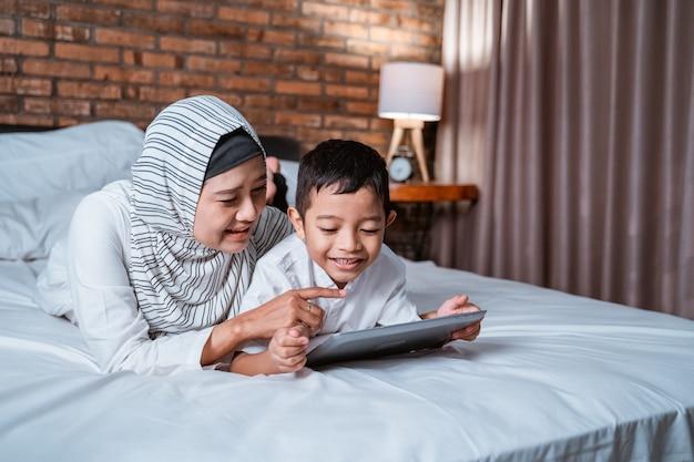 Moeder en zoon die tablet op het bed gebruiken