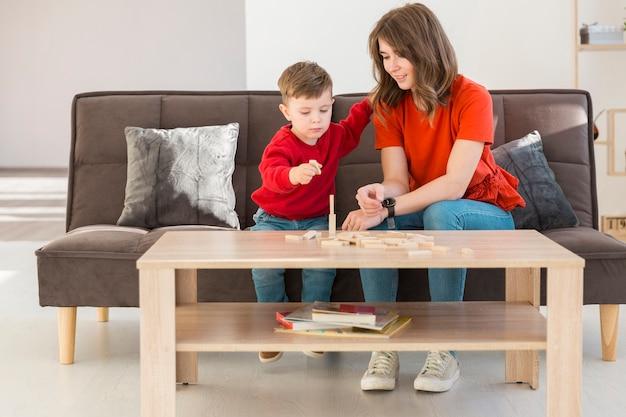 Moeder en zoon die thuis janga-spel spelen