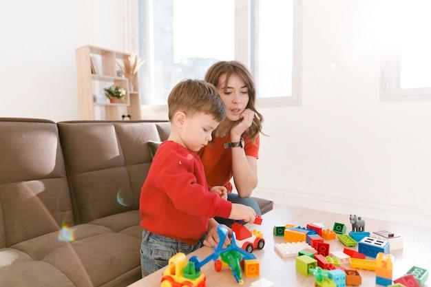 Moeder en zoon die thuis met speelgoed spelen