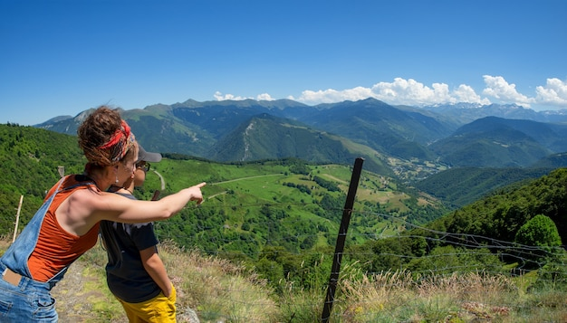 Moeder en zoon die uitzicht op de vallei aure in de franse pyreneeën kijken