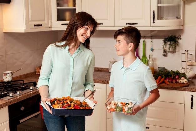 Moeder en zoon die voedsel in kichen voorbereiden