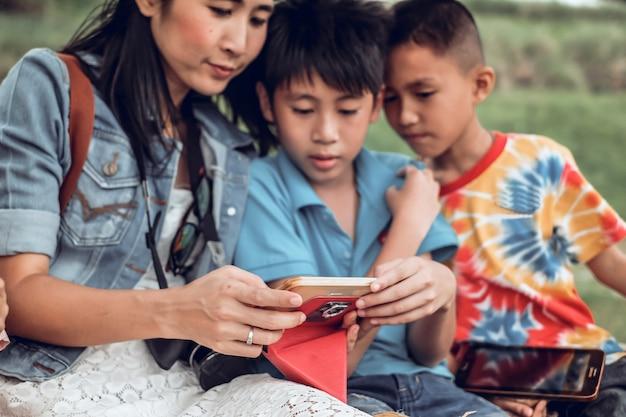 Moeder en zoon die voor het gebruiken van mobiele telefoon genieten van