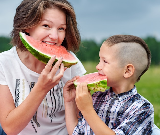 Moeder en zoon die watermeloen in weide of park eten. gelukkige familie op picknick. buiten portret