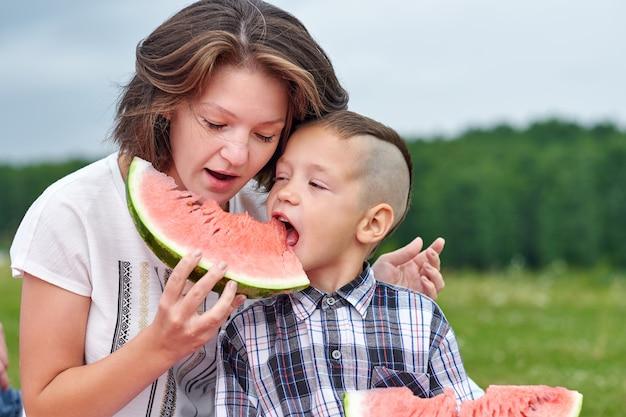 Moeder en zoon die watermeloen in weide of park eten. gelukkige familie op picknick. outdoor portret kleine jongen en moeder