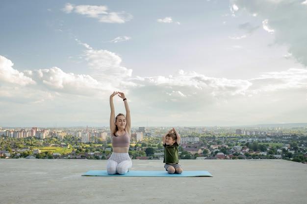 Moeder en zoon doen oefening op het balkon op de achtergrond van een stad tijdens zonsopgang of zonsondergang, concept van een gezonde levensstijl.