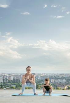 Moeder en zoon doen oefeningen op het balkon in de muur van een stad tijdens zonsopgang of zonsondergang