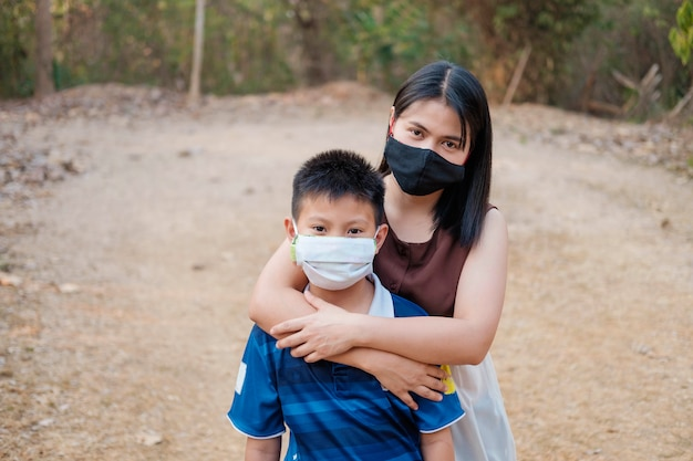 Moeder en zoon dragen een masker om het virus te beschermen. covid-19