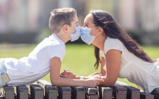 Moeder en zoon dragen witte t-shirts en gezichtsmaskers, liggend op hun buik op een bank buiten, oog in oog, met neuzen die elkaar raken.