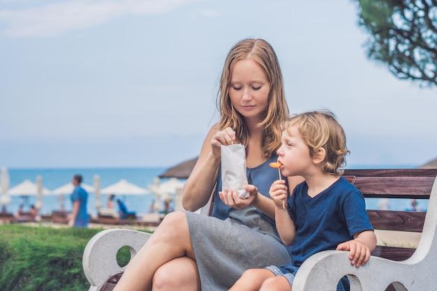 Moeder en zoon eten gebakken zoete aardappelen in het park. junkfood concept.