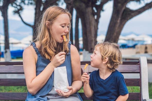 Moeder en zoon eten gebakken zoete aardappelen in het park
