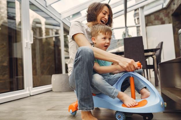 Moeder en zoon gaan rond in het appartement op een speelgoedauto