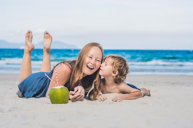 Moeder en zoon genieten van het strand en drinken kokosnoot.