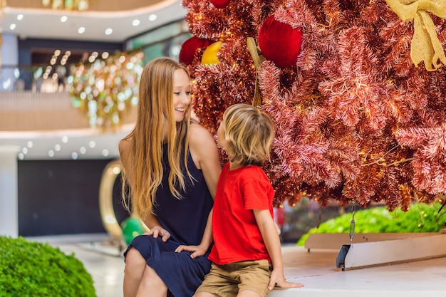 Moeder en zoon hangen een versiering aan de rode kerstboom