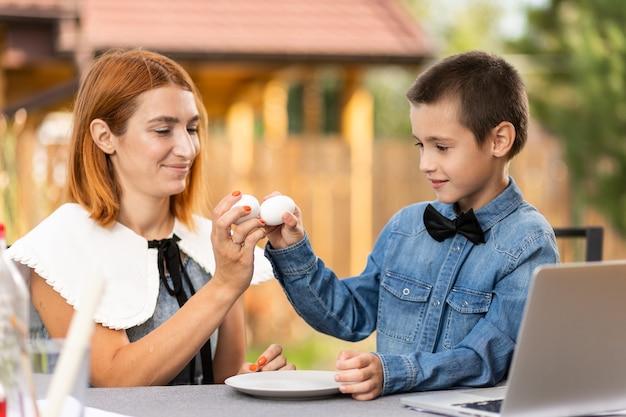 Moeder en zoon hebben plezier en slaan eieren op paasochtend. pasen voor het hele gezin. heeft plezier tijdens de voorbereiding voor pasen.