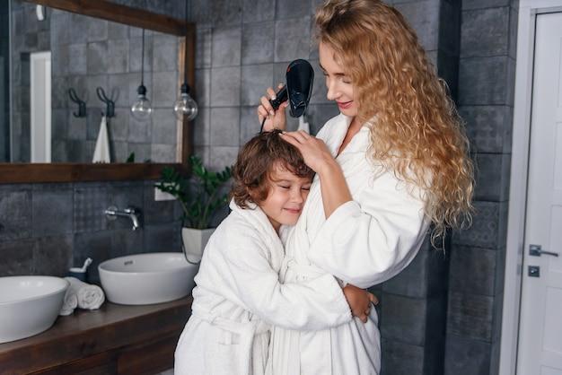 Moeder en zoon hebben samen plezier in de badkamer. mooie moeder met haar zoontje gekleed in badjas ontspannen en spelen samen in de badkamer.