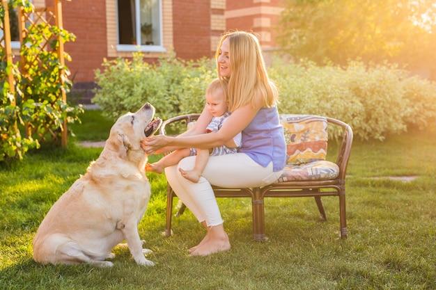 Moeder en zoon hebben samen plezier in het zomerpark en spelen met een golden retriever.