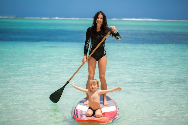 Moeder en zoon hebben surfen in de oceaan op het bord