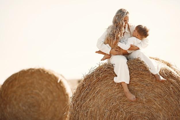 Moeder en zoon. hooistapel of baal op geel tarwegebied in de zomer. kinderen hebben samen plezier.