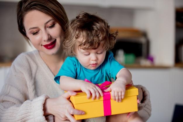 Moeder en zoon houden een geschenkdoos voor kerstmis