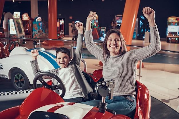 Moeder en zoon in amusementscentrum en handen omhoog