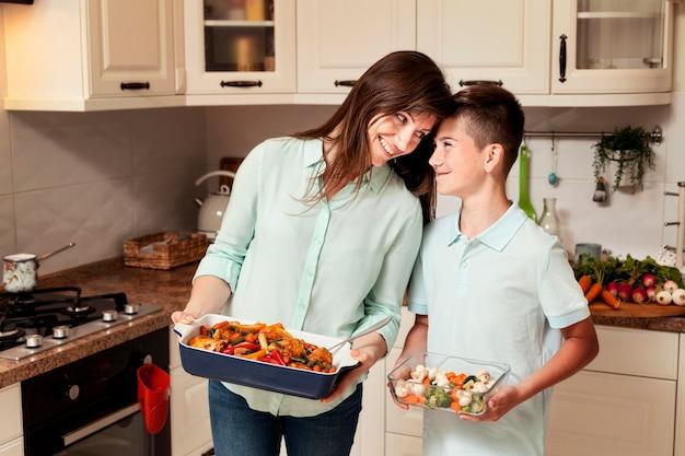 Moeder en zoon in de keuken die voedsel voorbereidt