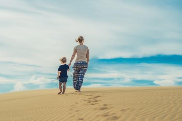 Moeder en zoon in de woestijn. reizen met kinderen concept.