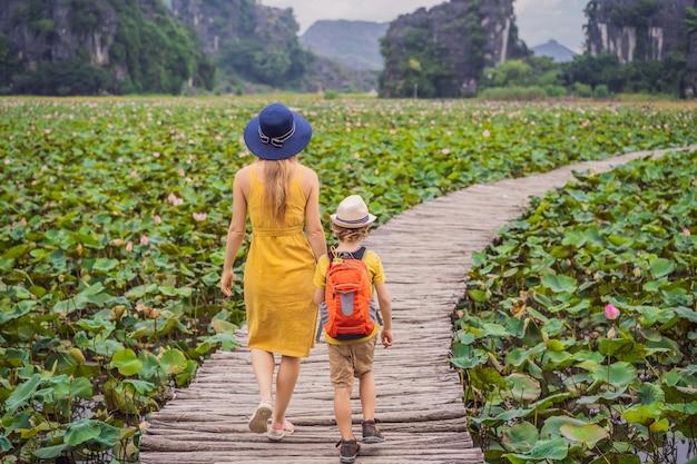 Moeder en zoon in een geel op het pad onder de lotusmeer mua grot ninh binh vietnam vietnam