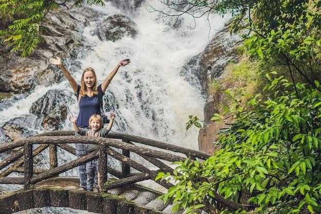 Moeder en zoon in het oppervlak van de prachtige trapsgewijze datanla waterval in het bergstadje dalat, vietnam