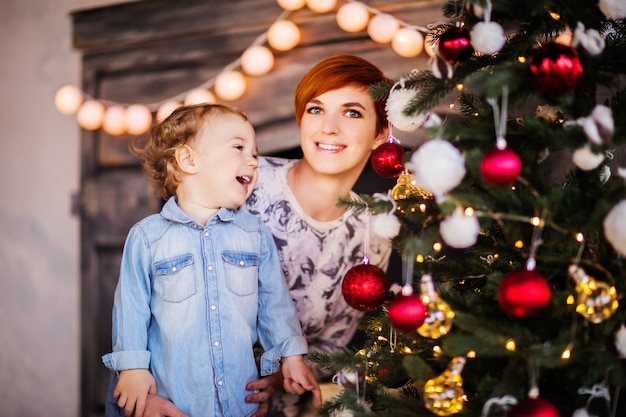 Moeder en zoon in kerstpyjama lachen tegen de achtergrond van een boom met een open haard. hoge kwaliteit foto