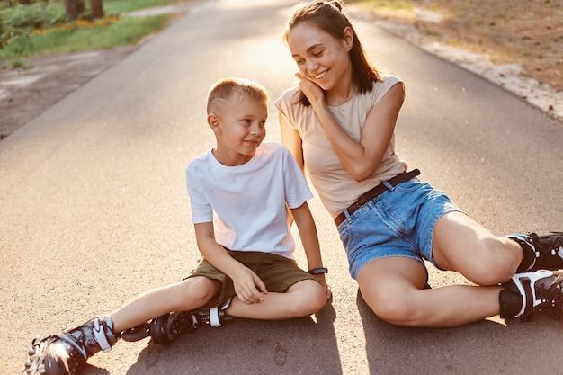 Moeder en zoon in rolschaatsen zittend op een weg, mama pratend met haar kleine jongen, genietend van prachtige natuur en frisse lucht, actieve weekenden samen.