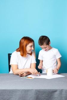 Moeder en zoon in witte t-shirts zijn bezig met tekenen met aquarellen op een blauwe achtergrond