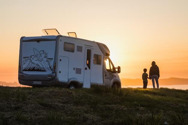 Moeder en zoon kijken naar de zonsondergang met hun camper aan de rand van de zee