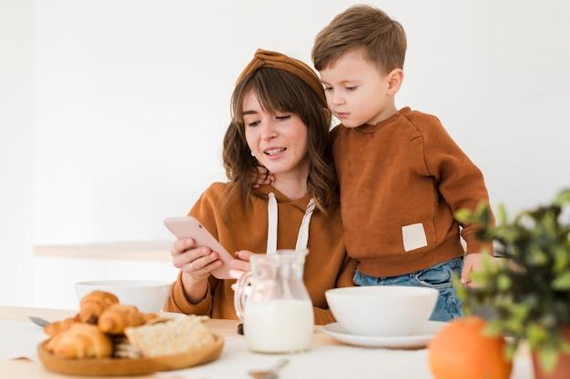 Moeder en zoon kijken op mobiel