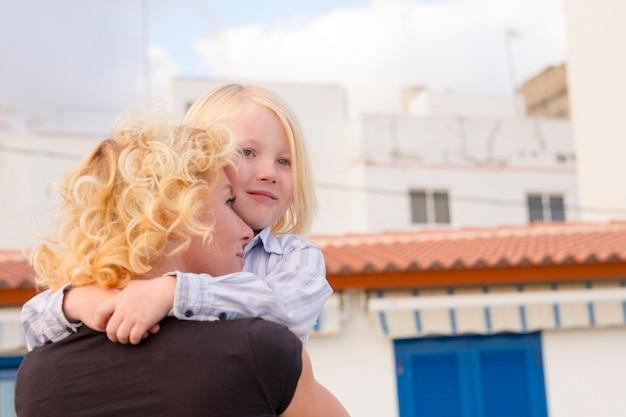Moeder en zoon kinderen knuffelen en liefhebben samen met geluk