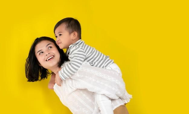 Moeder en zoon knuffelen, lachen en spelen samen op gele achtergrond. gelukkige familie momenten.
