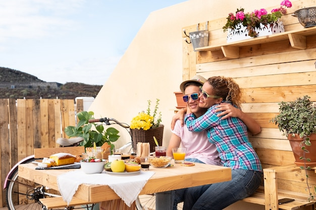 Moeder en zoon knuffelen met liefde buiten op het terras ontbijten. houten achtergrond. tafel vol fruit en cake. planten en bloemen op achtergrond