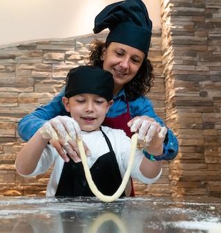 Moeder en zoon koken samen een gebakje in kokskostuums