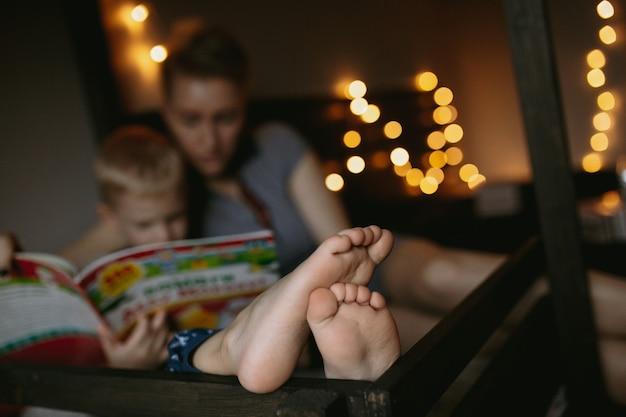 Moeder en zoon lezen een boek jongensvoeten op voorgrondafbeelding met selectieve focus